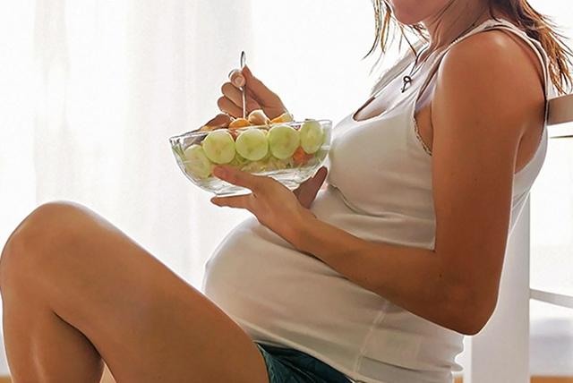 mujer embarazada de 35 semanas comiendo ensalada