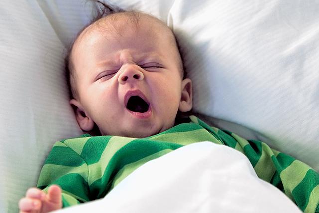 bebé bostezando vestido de verde