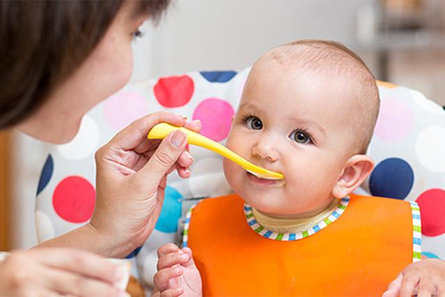 bebé con babero naranja comiendo con una cucharita