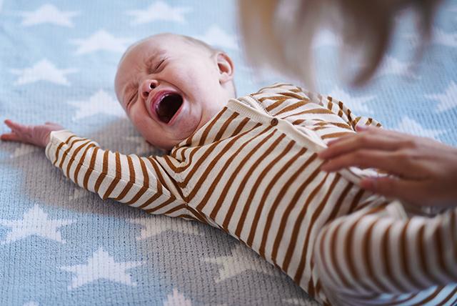 bebé de rayas llorando