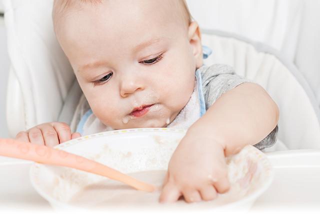 bebé metiendo la mano en tazón de papilla