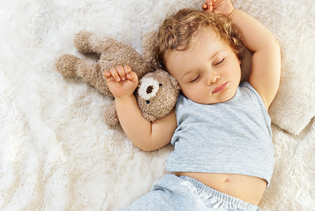 bebé vestido de azul durmiendo con osito de peluche