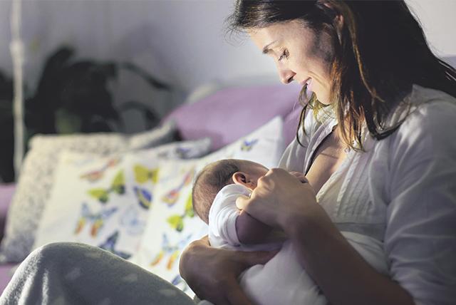 mamá amamantando bebé ambos vestidos de blanco