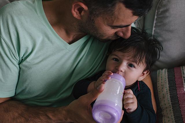 papá alimentando a su bebé con biberón