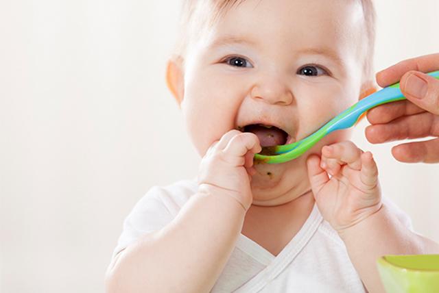 bebé sonriente comiendo con cuchara