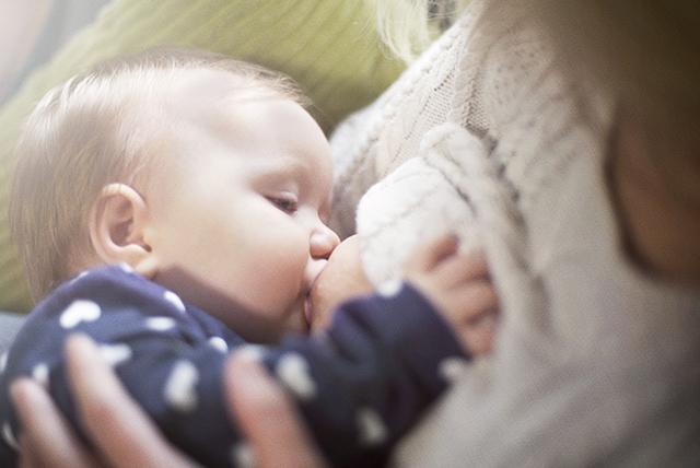 Bebé con ijama azul lactando